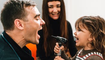 Child playfully holding out otoscope to check doctor