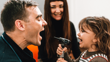 Child playfully holding otoscope with doctor and parent