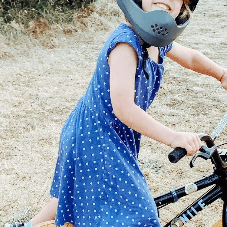 Picture of smiling child wearing a helmet on a bicycle