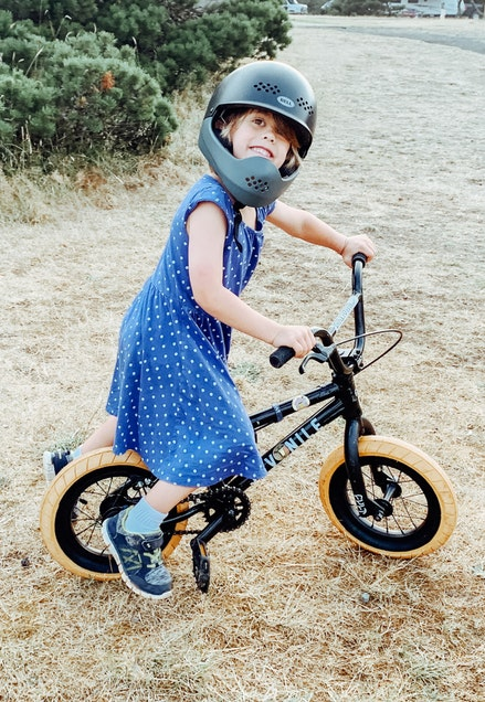 A little girl wearing a helmet while on a bike