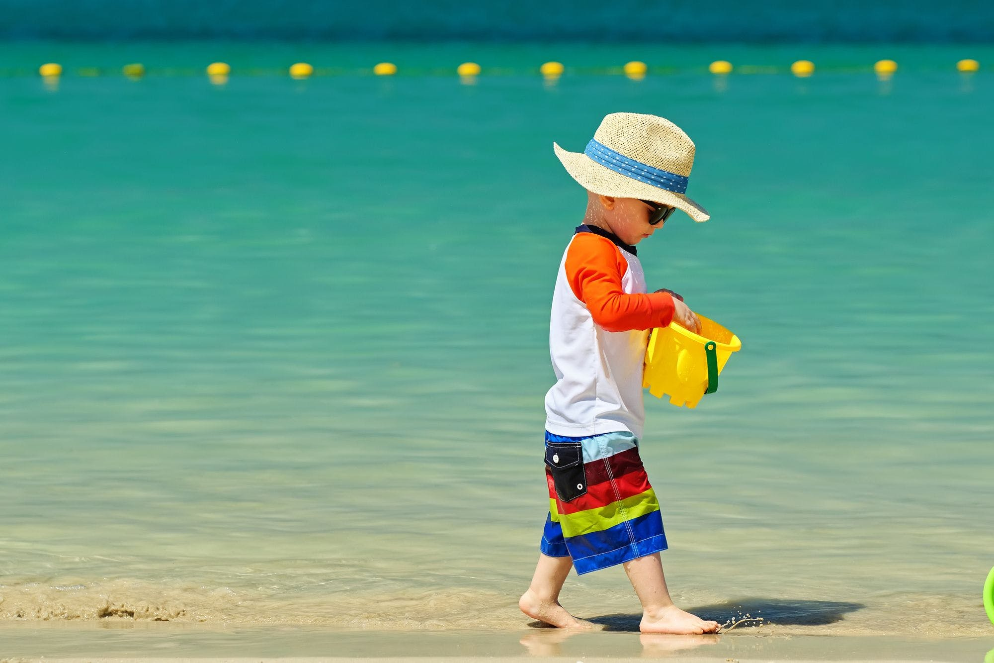 Small child wearing a hat and sunglasses, carries a pail while walking along the shore at a beach.