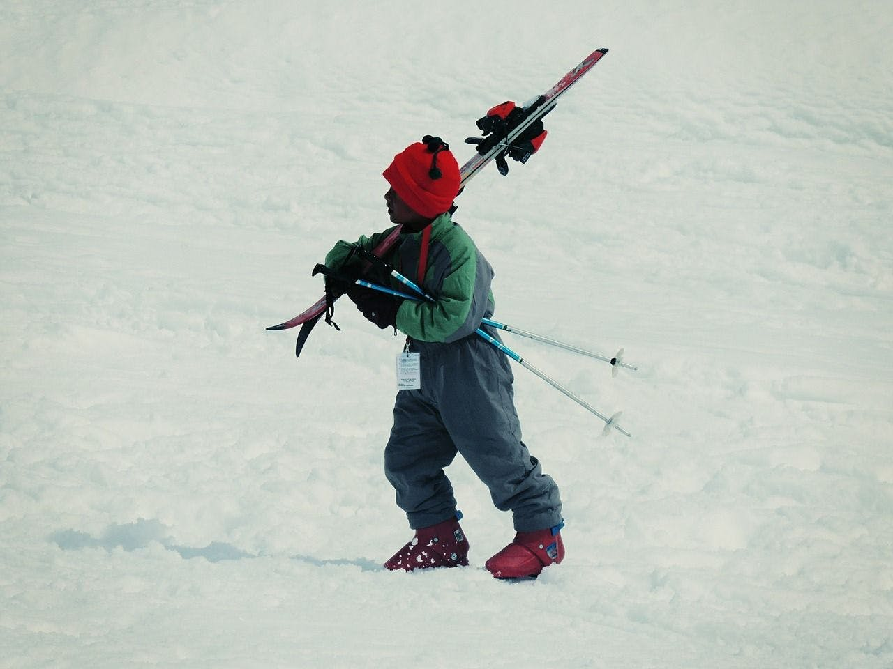 A child walks through the snow with skis.