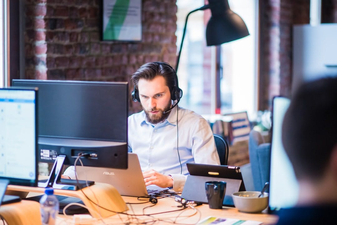Man with a headset sitting in front of a laptop in office. approachable, friedly team, support