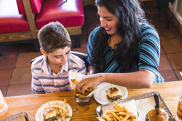 Mother and son enjoying Chili's burgers and fries.