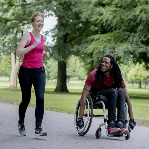 Man in a wheelchair next to a woman running, both smiling together