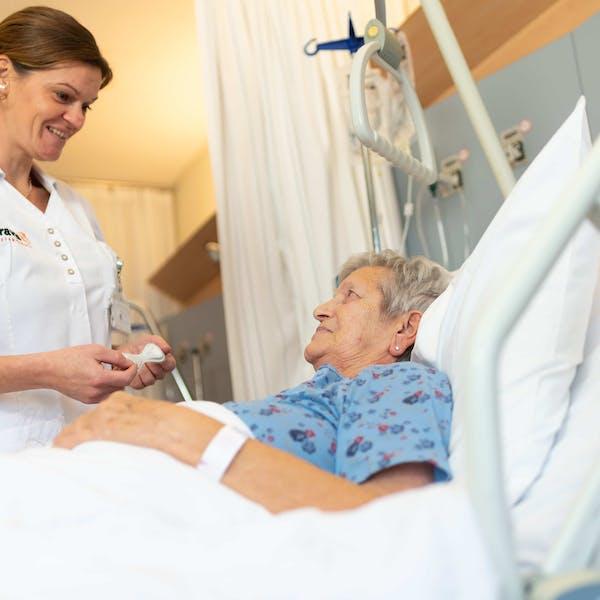 Oudere mevrouw die hulp krijgt in ziekenhuis