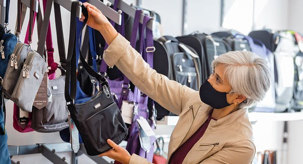 CAA Member browsing purses at CAA Store with face mask on