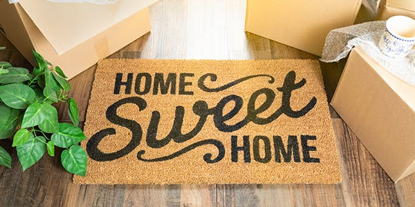 Image of a door mat saying Home Sweet Home surrounded by moving boxes