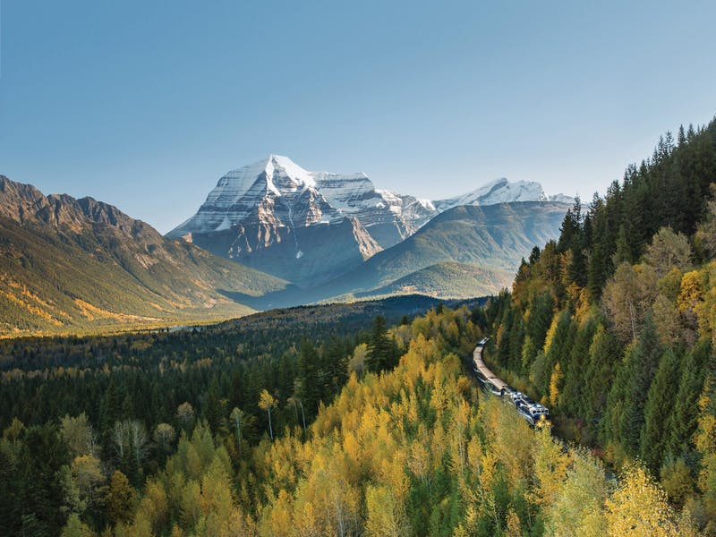 Rocky Mountaineer carving through lush forests and mountains