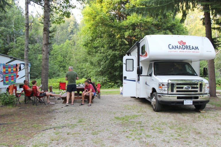 CanaDream RV parked at a campsite with family sitting outside