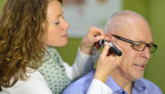 A woman looking inside a man's ear