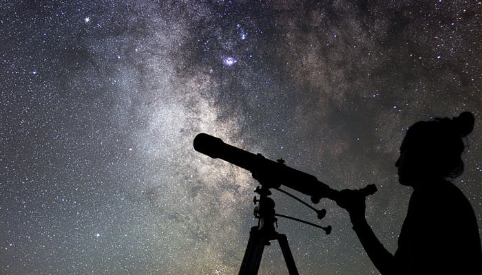 Woman looking through a telescope at the stars
