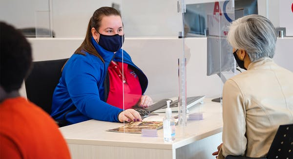 CAA Travel Consultant assisting CAA Member at CAA Store with face masks on