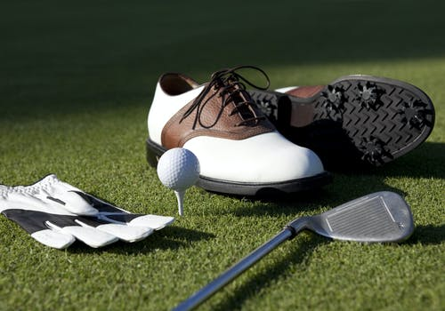 Golf shoes, club, glove and golf ball on a tee