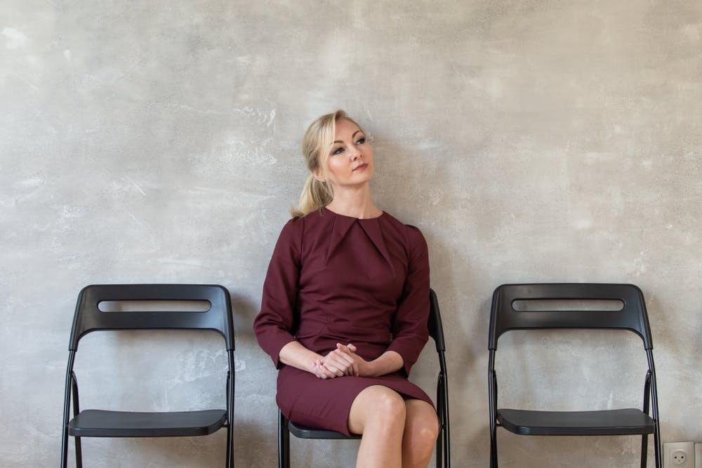 Femme portant une robe de couleur bordeaux pour un entretien d'embauche