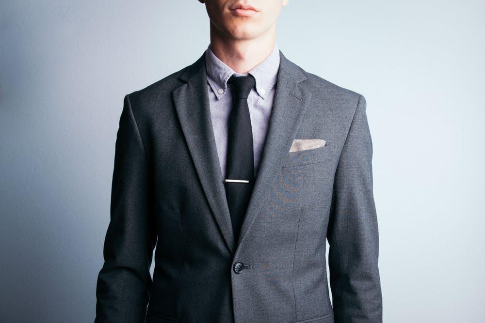 Homme portant un costume gris avec une cravate pour un entretien d'embauche