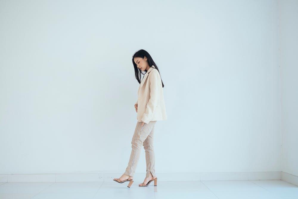 Femme portant un pantalon et une veste beiges avec des talons