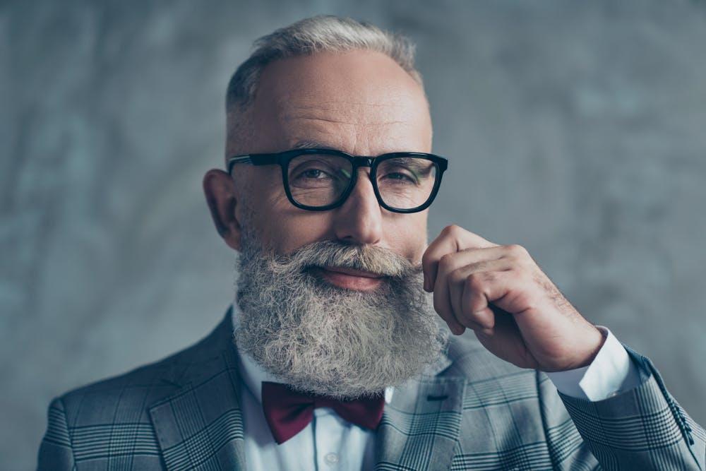 Homme élégant avec des lunettes et une barbe bien taillée