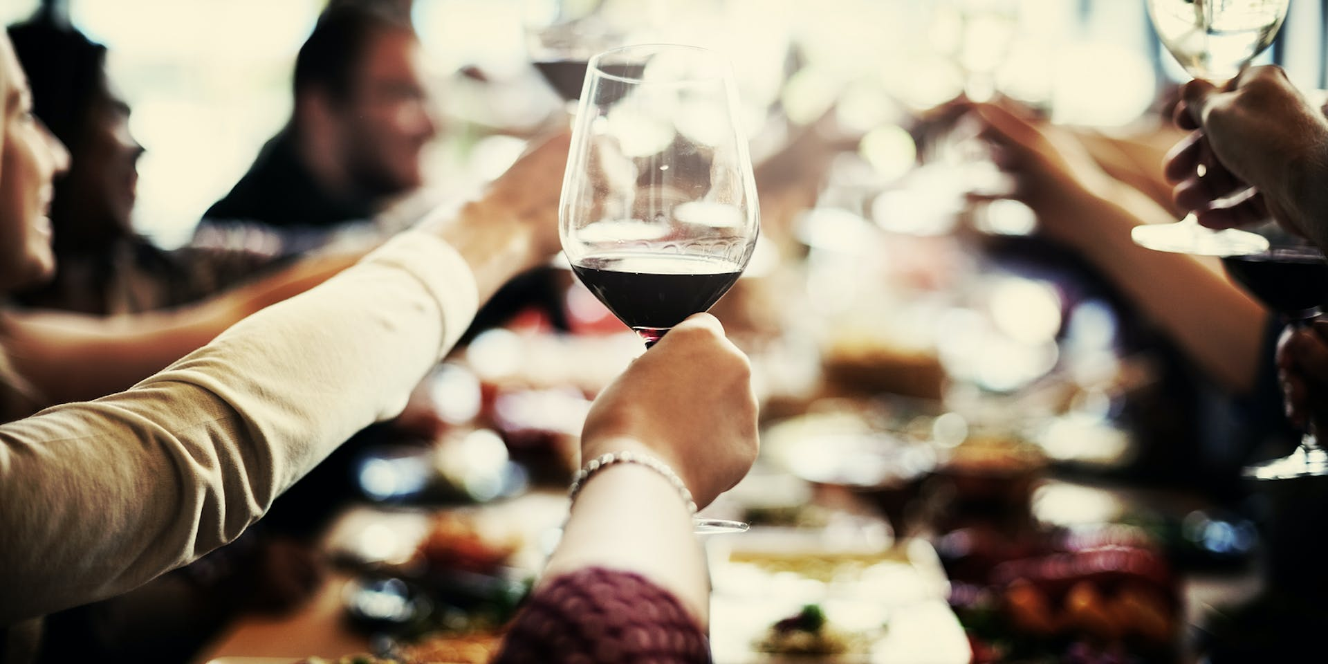 Group sitting around a table raising their wine glasses in a toast.
