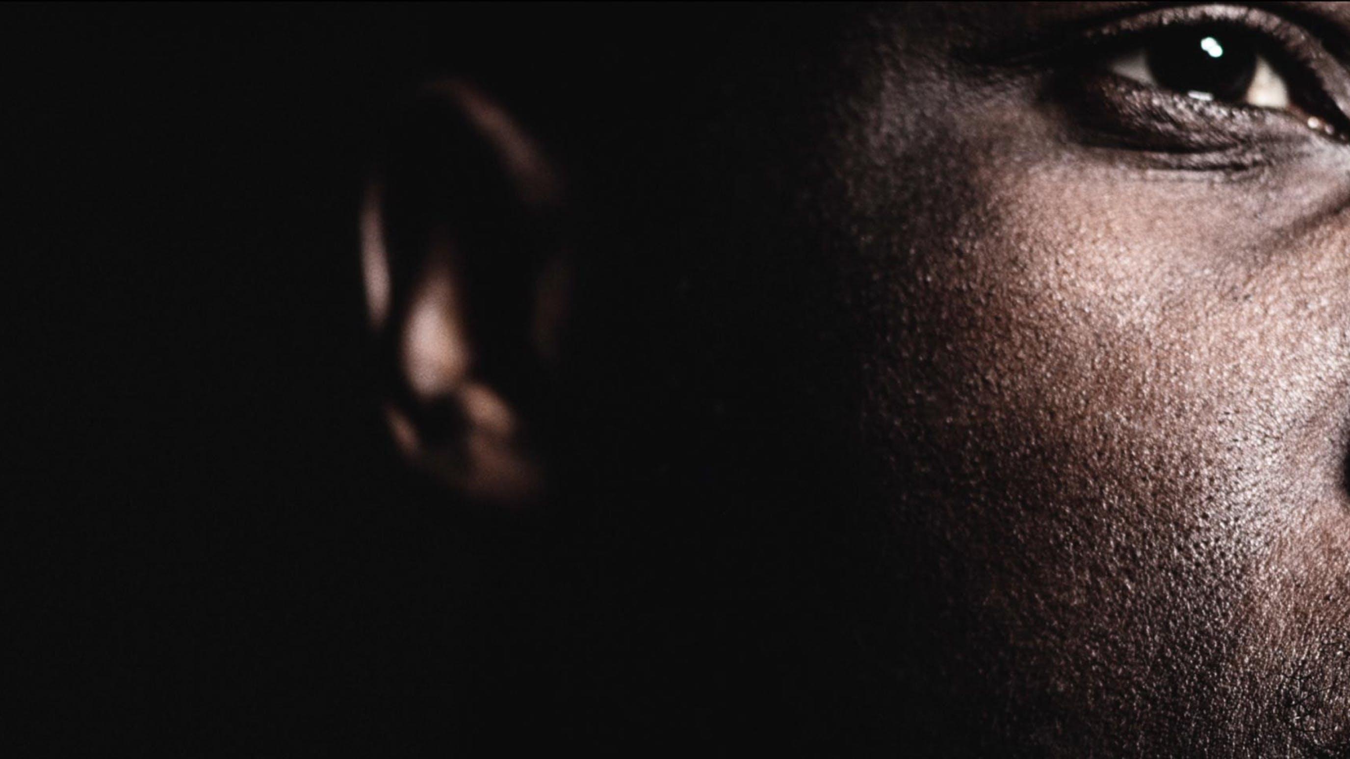super close-up of side of person's face in front of a black background