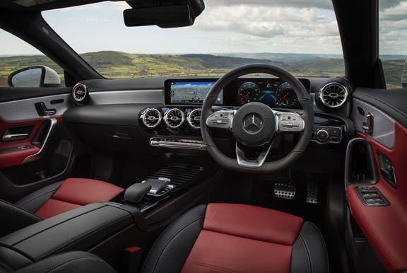 The interior of a Mercedes-Benz CLA with steeringwheel and dashboard in shot