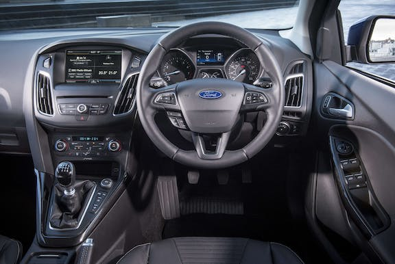 The interior of a Ford Focus with steering wheel and dashboard in shot