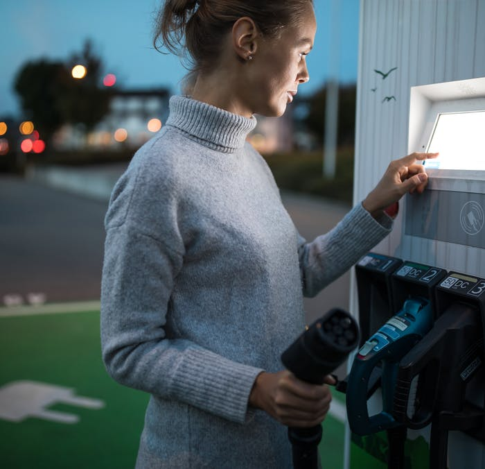 A woman at an electric car charging station