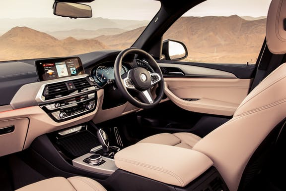 The interior of a BMW X3 with steeringwheel and dashboard in shot