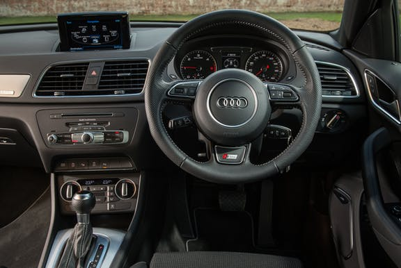 The interior of an Audi Q3 with steeringwheel and dashboard in shot