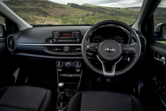 The interior of a Kia Picanto with steering wheel and dashboard in shot