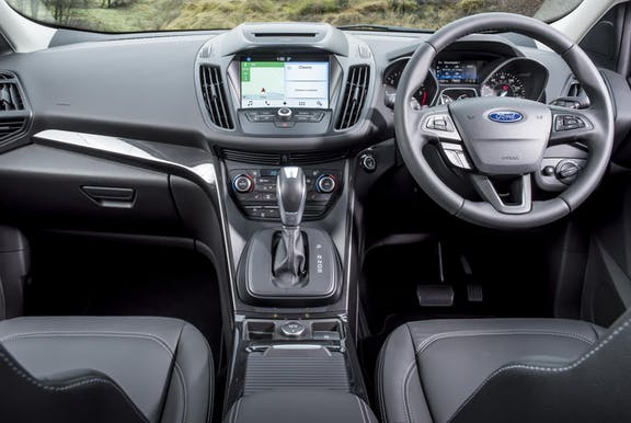 The interior of a Ford Kuga with steeringwheel and dashboard in shot