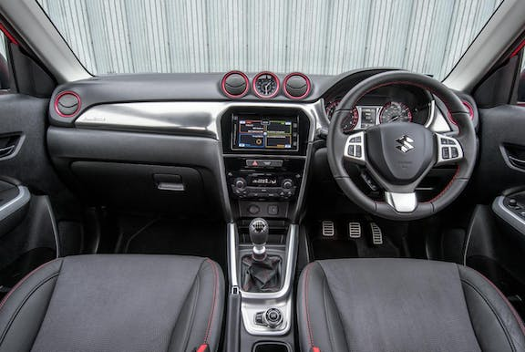 The interior of a Suzuki Vitara with steering wheel and dashboard in shot