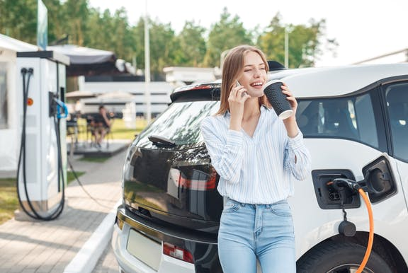 Electric cars being charged with woman smiling