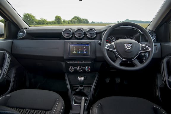 The interior of a Dacia Duster with steering wheel and dashboard in shot