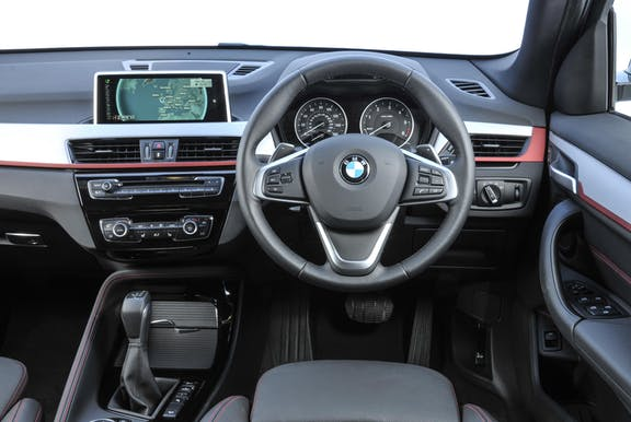 The interior of a BMW X1 with steering wheel and dashboard in shot