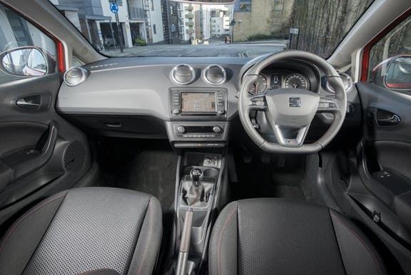 The interior of a Seat Ibiza with steeringwheel and dashboard in shot