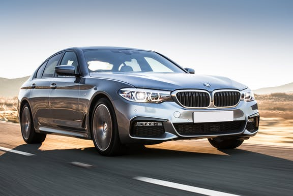 The front exterior of a silver BMW 5 Series