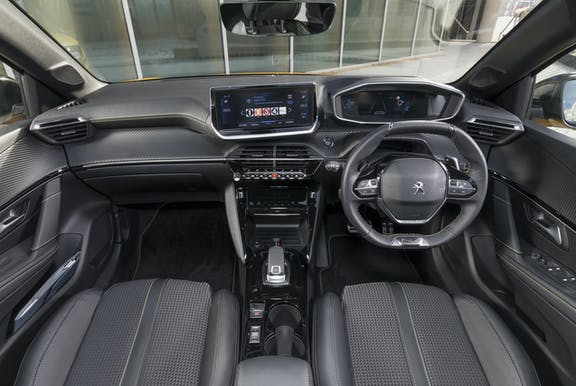 The interior of a Peugeot 208 with steering wheel and dashboard in shot