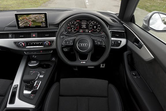 The interior of an Audi A5 with steeringwheel and dashboard in shot