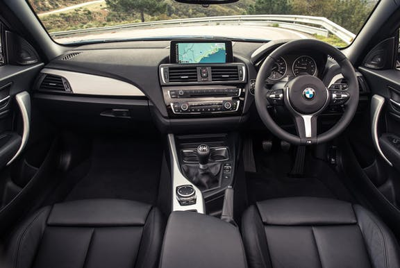 The interior of a BMW 2-Series with steering wheel and dashboard in shot