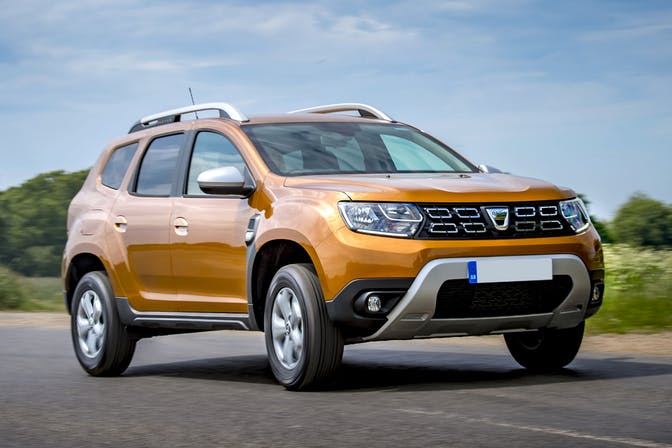 The front exterior of a gold Dacia Duster