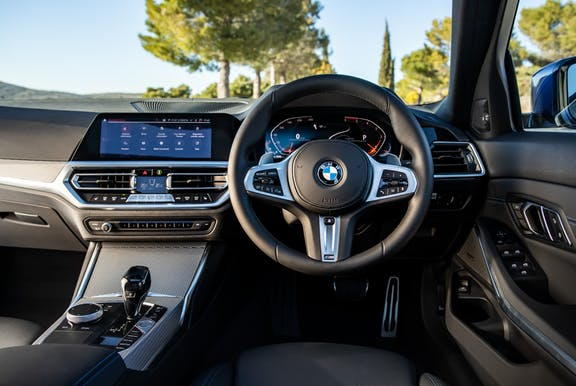 The interior of a BMW 3 Series with steering wheel and dashboard in shot