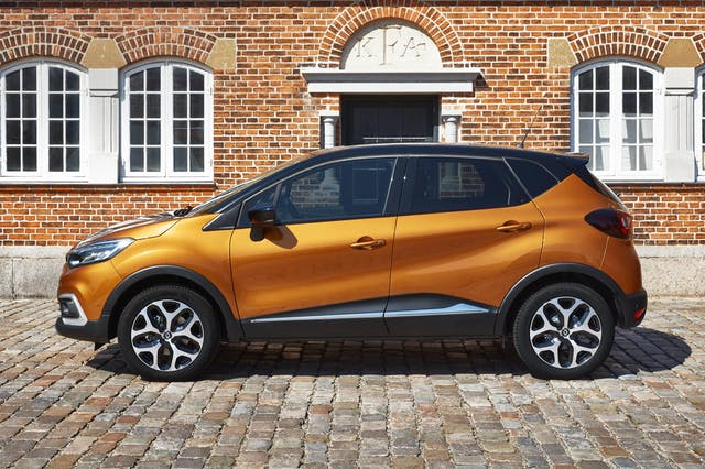 The side exterior of a yellow Renault Captur