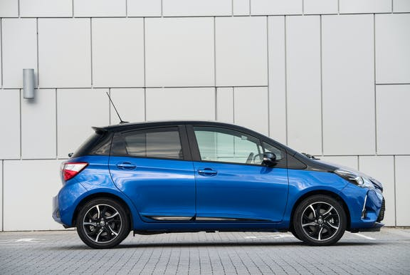 The side exterior of a blue Toyota Yaris