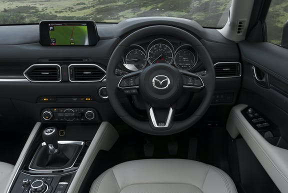 The interior of a Mazda CX-5 with steering wheel and dashboard in shot