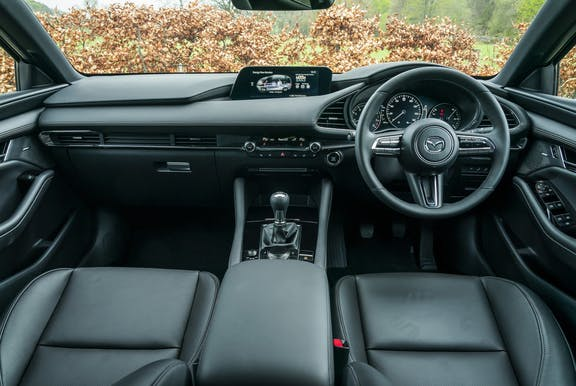 The interior of a Mazda 3 with steering wheel and dashboard in shot