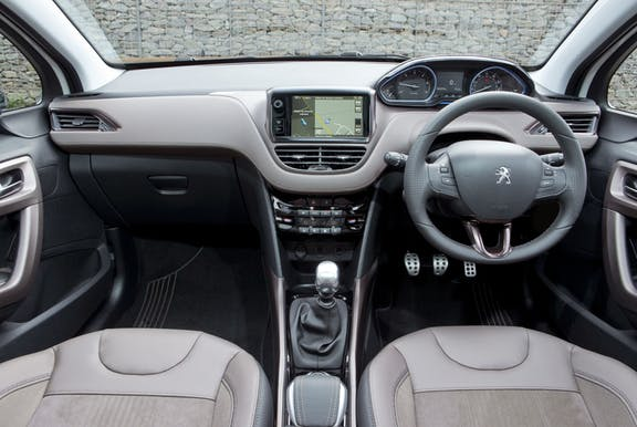 The interior of a Peugeot 2008 with steering wheel and dashboard in shot