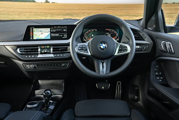 The interior of a BMW 1 Series with steering wheel and dashboard in shot