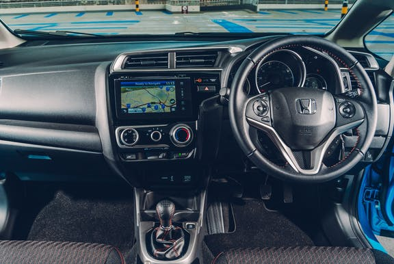 The interior of a Honda Jazz with steeringwheel and dashboard in shot