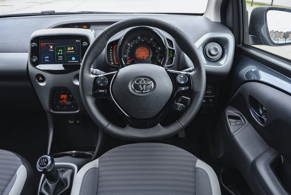 The interior of a Toyota Aygo with steering wheel and dashboard in shot